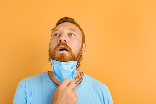 あごひげと入れ墨のある男は、covidのマスクを削除します