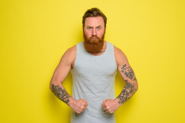 수염과 문신을 한 남자가 근육을 자랑스럽게 보여줍니다.