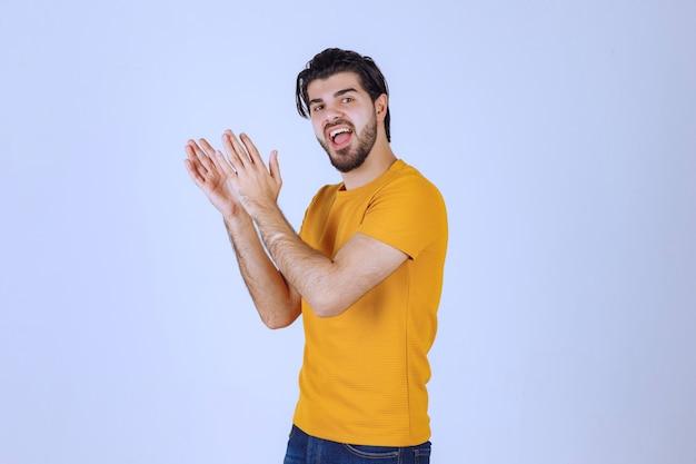 Человек с бородой что-то аплодирует
