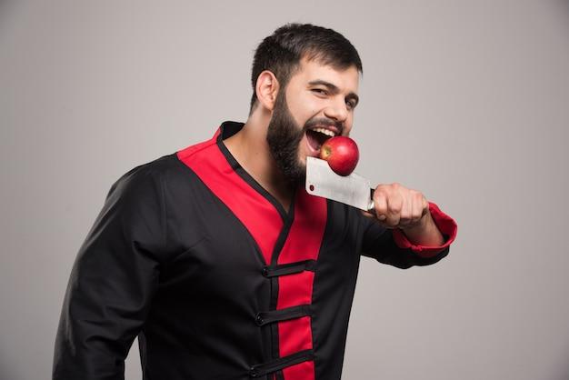 Человек с бородой кусает красное яблоко на нож.