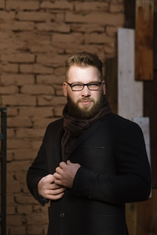 A man with a beard in a black warm coat with a scarf poses to advertise men's clothing in the winter. advertise men's clothing