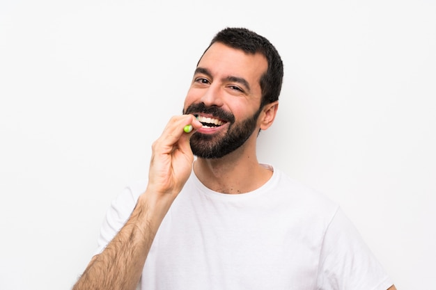 Man with beard brushing teeth over isolated white