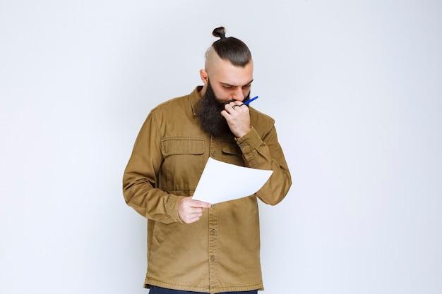 Uomo con la barba che controlla l'elenco dei progetti e segna note o correzioni.