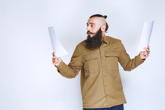 Uomo con la barba che controlla l'elenco dei progetti e segna note o correzioni. Foto Gratuite