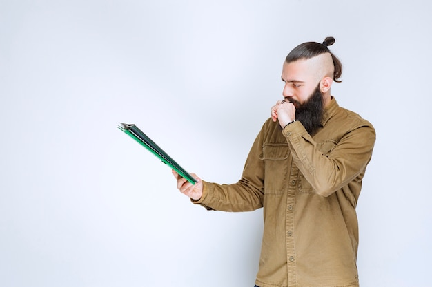 Man with beard checking the project list and marking notes or corrections.