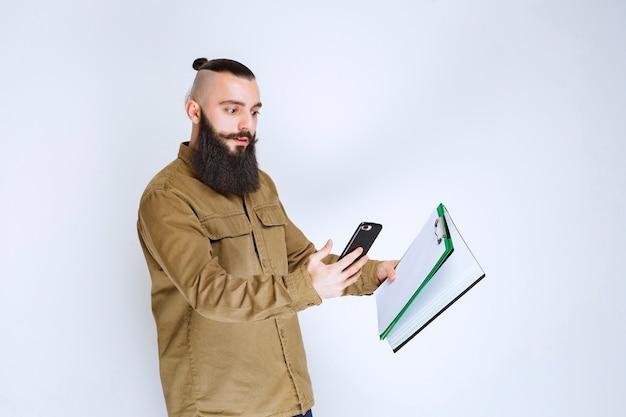 会計報告書をチェックし、電話で計算するあごひげを生やした男。