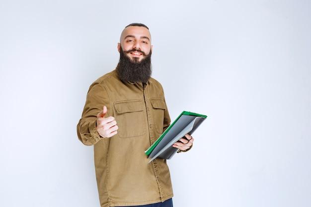 プロジェクトリストをチェックし、満足しているように見えるひげを持つ男。