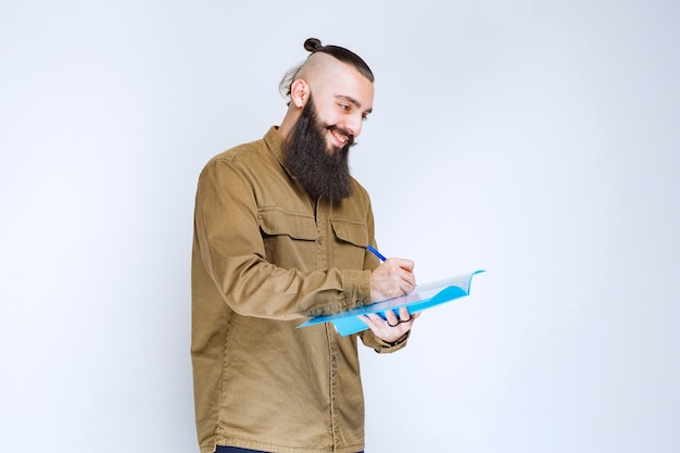 Мужчина с бородой проверяет список проектов и делает отметки или исправления.