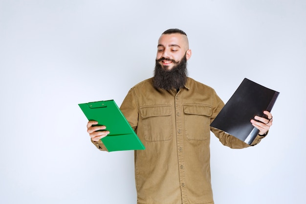 Man with beard checking two different projects to choose the winner.