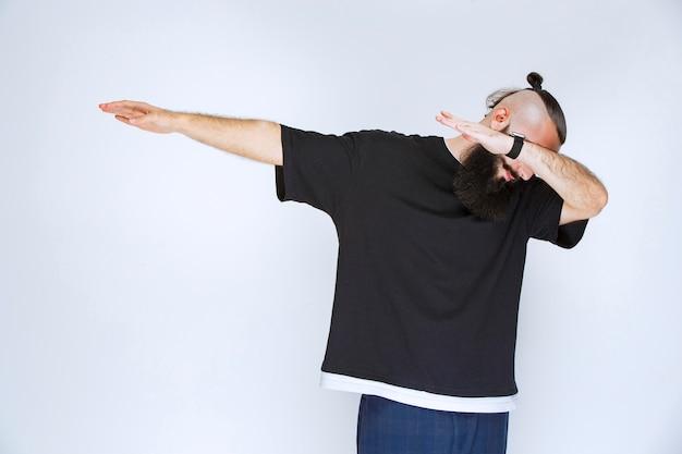 Uomo con la barba che balla o dà pose straordinarie.