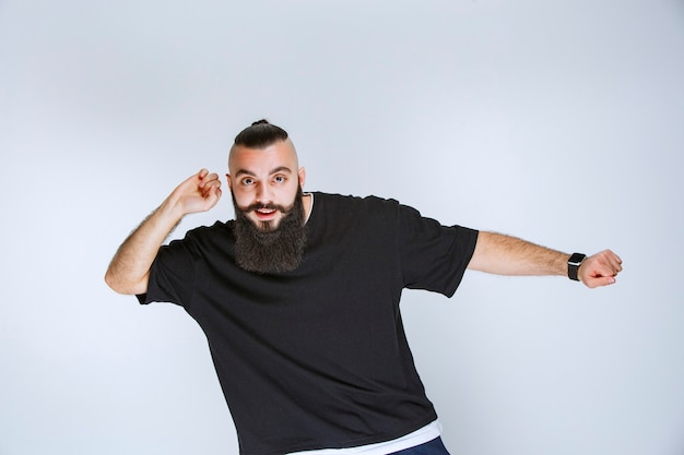 Man with beard dancing or giving extraordinary poses.