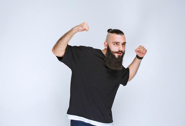 あごひげを生やした男性が腕の筋肉を示し、力強く感じています。