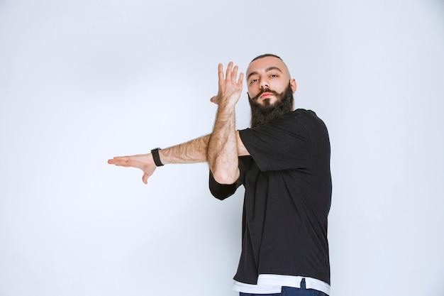 Мужчина с бородой демонстрирует мышцы рук и чувствует себя сильным.