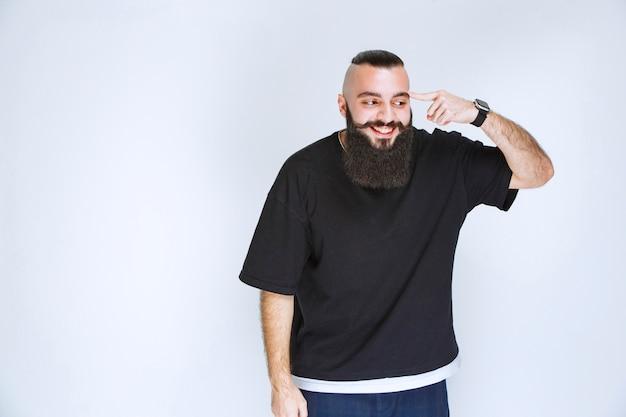Мужчина с бородой демонстрирует мышцы рук и кулаки.