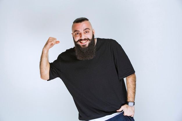 Man with beard demonstrating his arm muscles and fists.