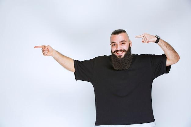 Uomo con la barba che dimostra i suoi muscoli e pugni del braccio.