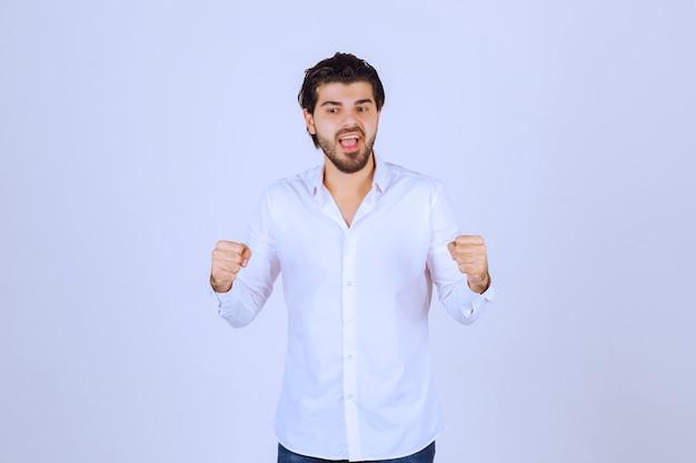 ひげを生やした男が拳と腕の筋肉を見せ、力強さを感じている。