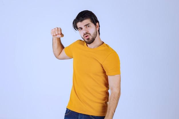 Uomo con la barba che mostra i muscoli del pugno e del braccio e si sente potente