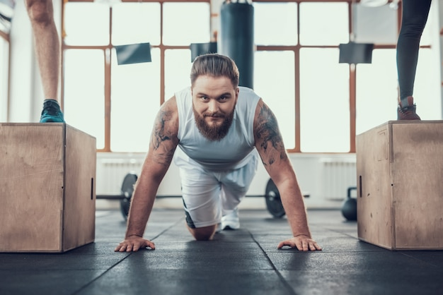 A man with a beard does exercise in the gym.