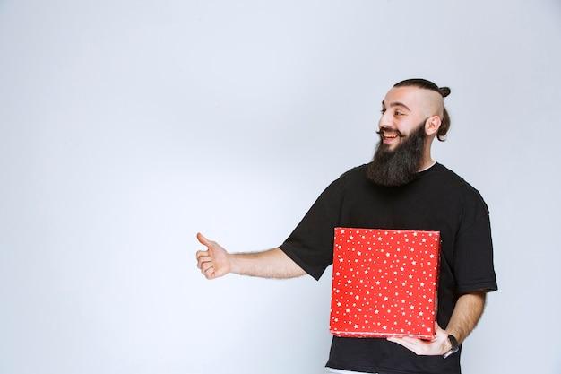 Uomo con la barba che si gode la sua confezione regalo rossa.