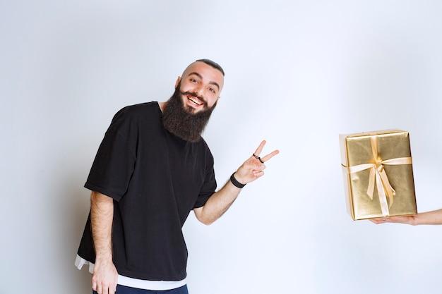 Мужчина с бородой доволен своей золотой дорогой подарочной коробкой.