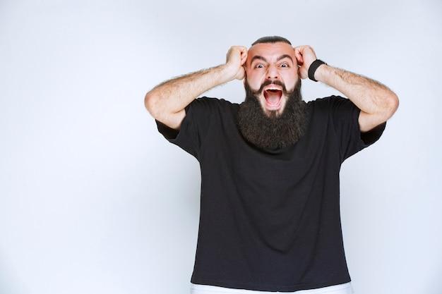 수염을 가진 남자는 예상치 못한 일 때문에 혼란스러워합니다.