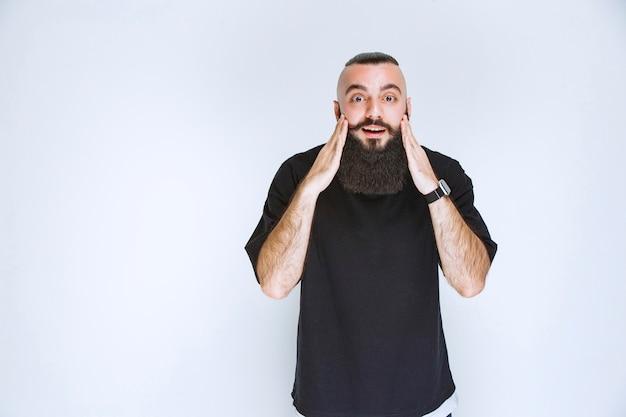 Человек с бородой из-за чего-то безумно счастлив.
