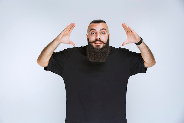 Man with beard gets extremely happy because of something.