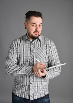 Man with beard graphic designer posing in studio with isolated gray photon with a graphic tablet
