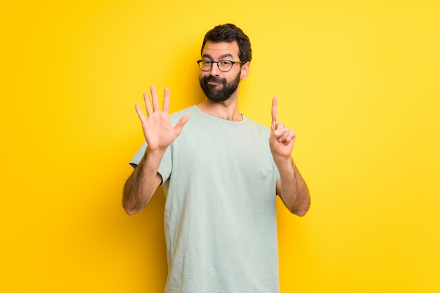 Man with beard and green shirt counting six with fingers