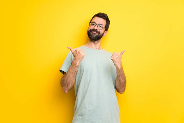 Man with beard and green shirt giving a thumbs up gesture with both hands and smiling