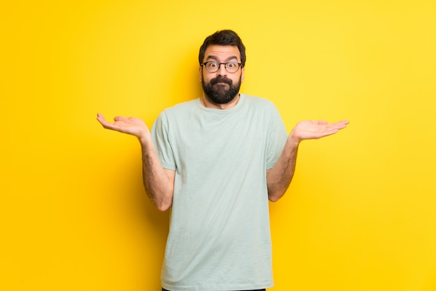 Man with beard and green shirt having doubts while raising hands and shoulders