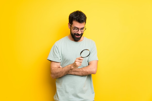 Man with beard and green shirt holding a magnifying glass