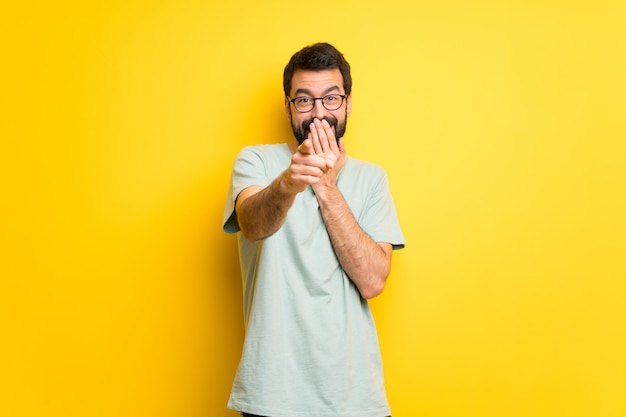 Man with beard and green shirt pointing with finger at someone and laughing