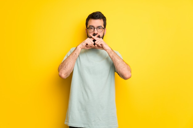 Man with beard and green shirt showing a sign of silence gesture