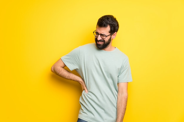 Man with beard and green shirt suffering from backache for having made an effort