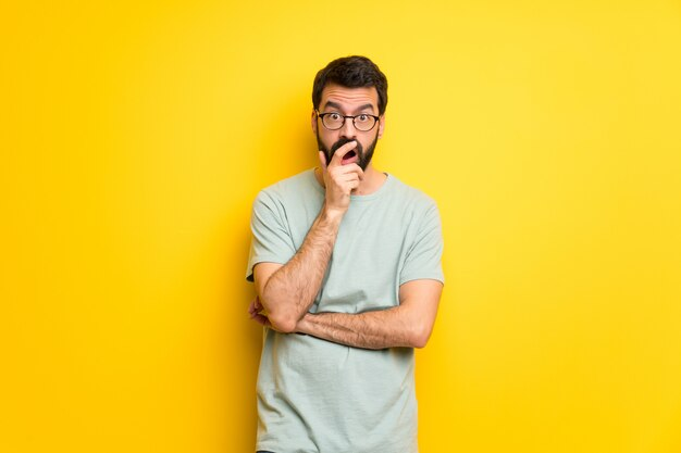 Man with beard and green shirt surprised and shocked while looking right