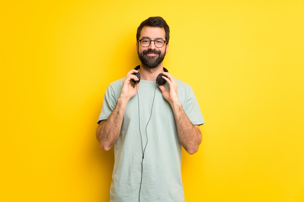 Man with beard and green shirt with headphones