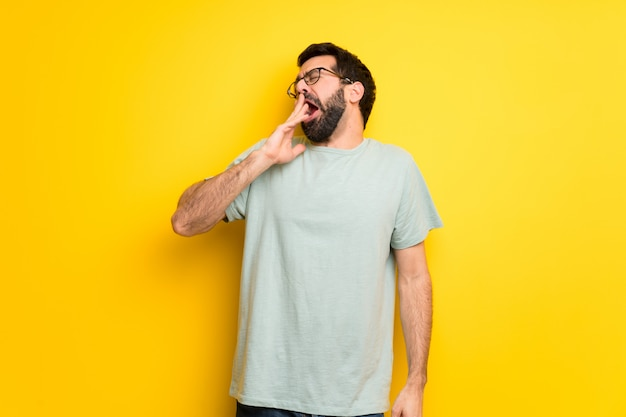 Man with beard and green shirt yawning and covering wide open mouth with hand