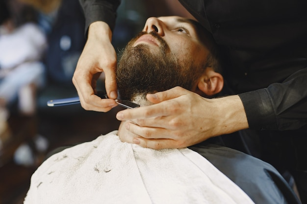 Man with a beard. hairdresser with a client. man with a shave.