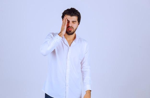수염을 가진 남자는 두통이 있고 아프다.