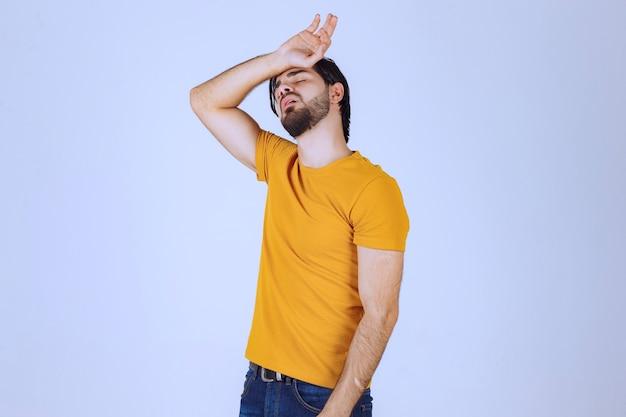 수염을 가진 남자는 두통이 있고 아프다