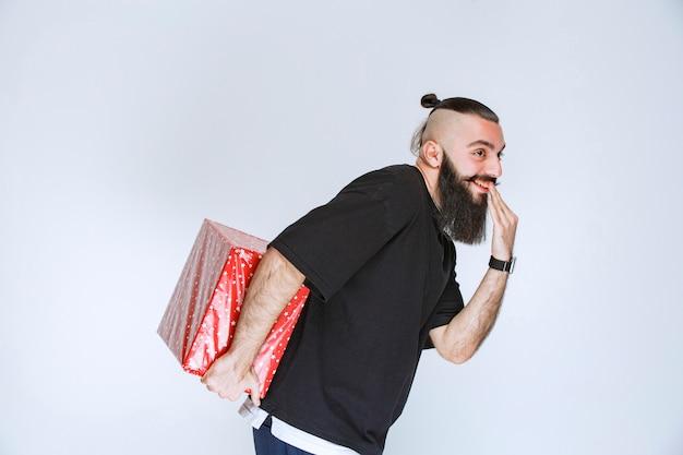 Мужчина с бородой прячет за собой красную подарочную коробку.