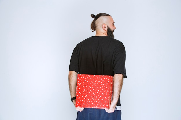 Uomo con la barba che nasconde una confezione regalo rossa dietro di sé.