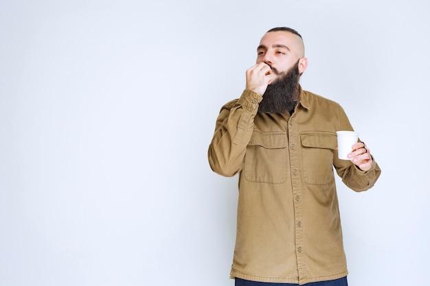 Мужчина с бородой держит чашку кофе и наслаждается вкусом.