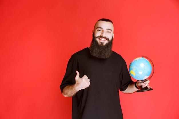 地球儀を持ってどこかを指しているひげを持つ男。