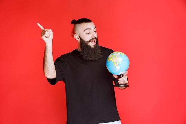 Человек с бородой держит глобус и указывает куда-то.