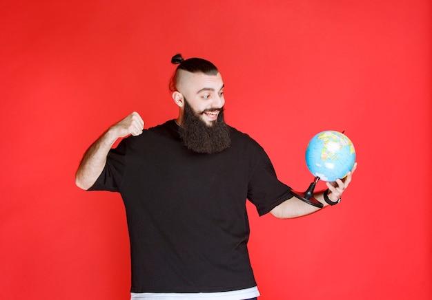 Человек с бородой держит глобус и показывает кулак.