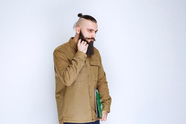 Мужчина с бородой держит викторину и выглядит растерянным и задумчивым.