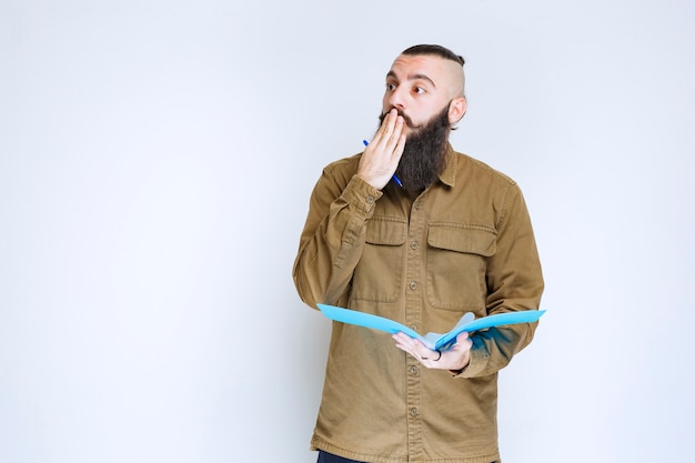 クイズ用紙を持っているあごひげを生やした男は、混乱して思慮深く見えます。